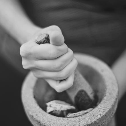 Die Hände einer Frau zerkleinern Blätter in einem Mörser.