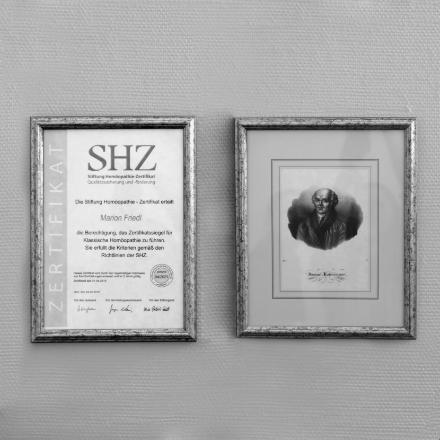 Ein Portrait von Hahnemann und das Stiftung Homöopathie-Zertifikat (SHZ) jeweils in einem Bilderrahmen an der Wand.