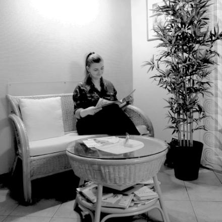 Eine junge Patientin sitzt im Wartezimmer der Heilpraktikerin Marion Friedl und blättert in einer Zeitung.
