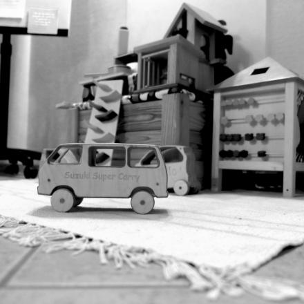 Ein Bus aus Holz steht vor mehr Holzspielzeug in der Kinder-Ecke der Heilpraxis.